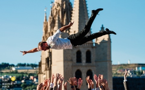 Guests toss the groom in the air in this photo by a Mende, France wedding photographer.