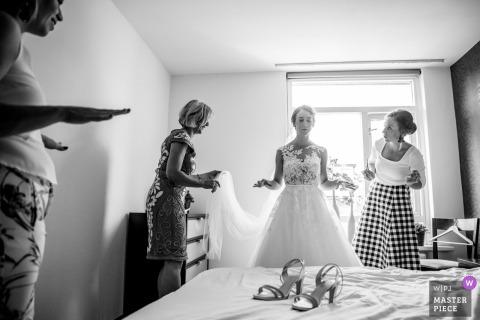 Schwarzweiss-Foto von zwei Frauen, die der Braut helfen, werden von einem Hochzeitsfotografen Enschede, die Niederlande angekleidet.