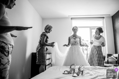 Black and white photo of two women helping the bride get dressed by a Enschede, Netherlands wedding photographer.