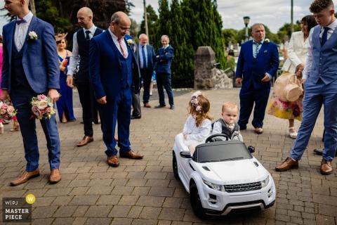 Auf diesem Foto eines Hochzeitsreportagefotografen aus Louth, Irland sehen Gäste zu, wie ein Junge und ein Mädchen in einem kleinen Auto fahren.