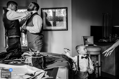 A little boy is called away as two men help each other get ready for the ceremony in this black and white photo by a Lake Tahoe, CA wedding photographer.