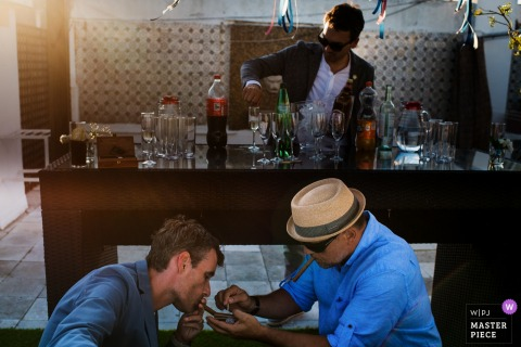 Photo of a man helping another light a cigarette in front of a bar in Lisbon by a Portugal wedding photographer.