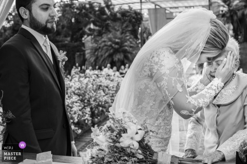 Black and white photo of the groom standing by the bride as she hugs an older woman by a Rio de Janeiro, Brazil wedding photographer.