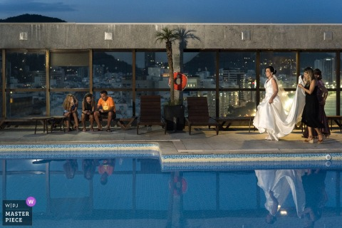 Guests hold the bride's train as she walks by a pool in Rio de Janeiro in this photo by a Brazil wedding photographer.