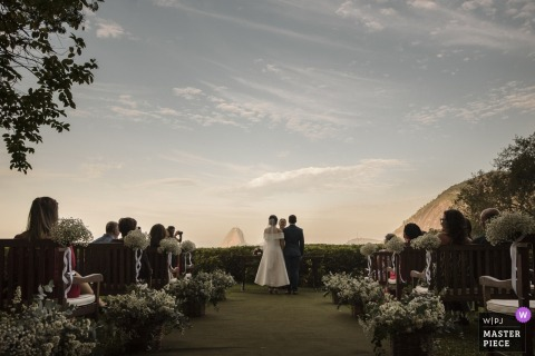 The bride and groom have their ceremony in a Rio de Janeiro garden as their guests watch in this photo by a Brazil wedding photographer.