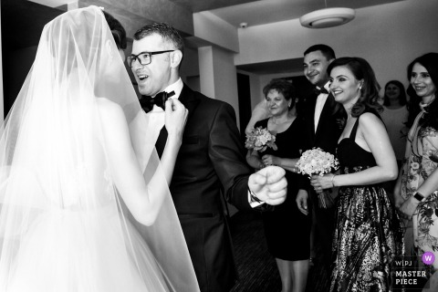 Black and white photo of the bride adjusting the groom's bow tie at their wedding in Slatina by a Romania wedding photographer.