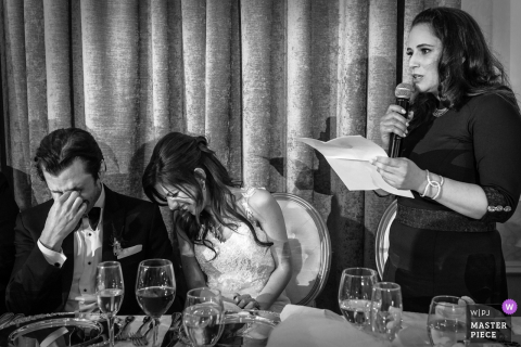 Black and white photo of the bride and groom laughing as a woman gives a speech by a Montreal, Quebec wedding photographer.
