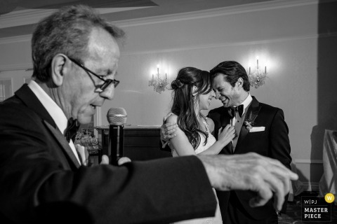 Black and white photo of the bride and groom holding each other and smiling as a man gives a speech by a Montreal, Quebec wedding photographer.