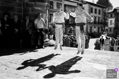 Two men in traditional dress perform in the cobblestone street in this black and white photo by a Biscay, Spain wedding photographer.