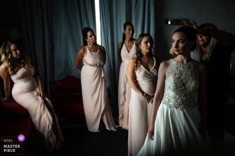 The bride stands with her bridesmaids as one of them takes photos in Villa la Vedetta in Tuscany in this photo by a Veneto, Italy wedding photographer.