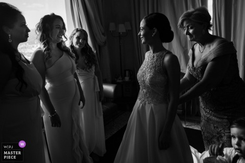 Black and white photo of the bridal party helping the bride with her dress in Villa la Vedetta in Tuscany by a Veneto, Italy wedding photographer.