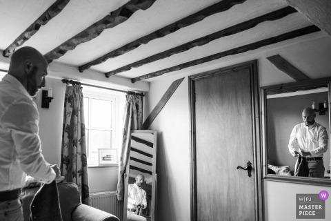Schwarzweiss-Foto des Bräutigams, der in seinem Raum vor einem Spiegel in Shropshire, Großbritannien von einem England-Hochzeitsfotografen fertig wird.