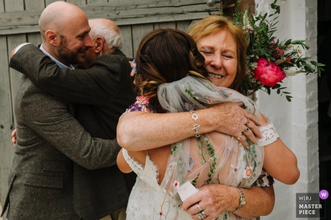 Photo of a man and woman hugging the bride and groom at their wedding in Shropshire, UK by a Lancashire, England wedding reportage photographer.