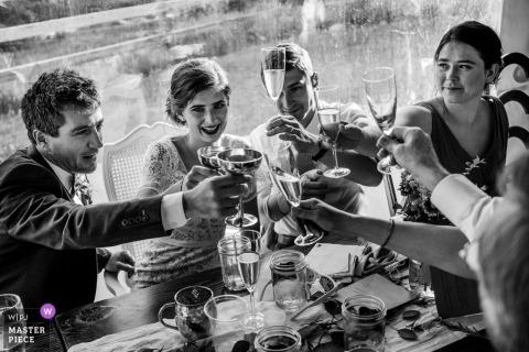 De bruid, bruidegom en gasten proosten elkaar op deze zwart-witfoto genomen in Leavenworth, WA door een trouwfotograaf van Seattle.