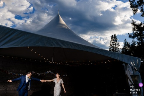 The bride and groom hold hands in front of a large tent in Leavenworth, WA in this photo by a Seattle wedding photographer.