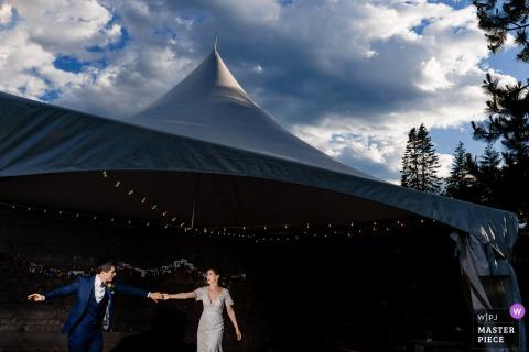 De bruid en de bruidegom dienen indienen voorzijde van een grote tent in Leavenworth, WA in deze foto door een het huwelijksfotograaf van Seattle in.