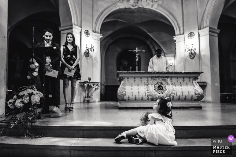The flower girl sits on a step in front of the altar in this black and white photo by a Paris wedding photographer.