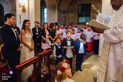 Photo of young children standing at the altar with the bride and groom by a Paris wedding photographer.