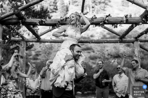 Black and white photo taken in Truckee, CA of the bride sitting on the groom's shoulders by a Lake Tahoe wedding photographer.