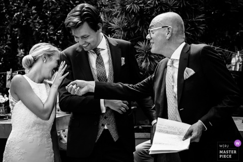 The bride hides her face in the groom's shoulder during the speech in Leiden in this black and white photo by a Netherlands wedding photographer.
