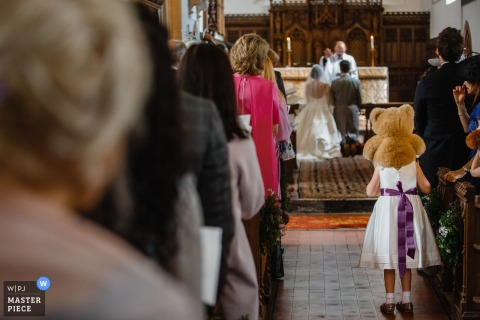 A young girl stands with a teddy bear on her shoulders as the bride and groom kneel at the altar in England in this photo by a St. Petersburg, Russia wedding photographer.