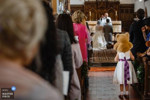 Een jong meisje bevindt zich met een teddybeer op haar schouders aangezien de bruid en het bruidegom knielen bij het altaar in Engeland in deze foto door een het huwelijksfotograaf van St. Petersburg, Rusland.