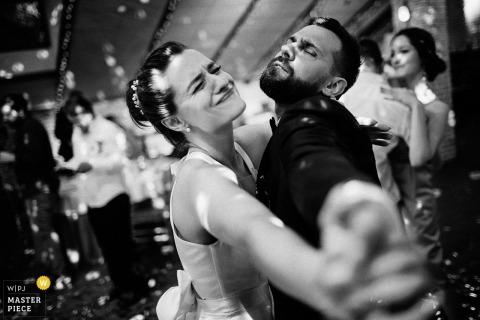 Zwart-witte foto van de bruid en de bruidegom die met hun wapens dansen uitgestrekt door een het huwelijksfotograaf van St. Petersburg, Rusland.