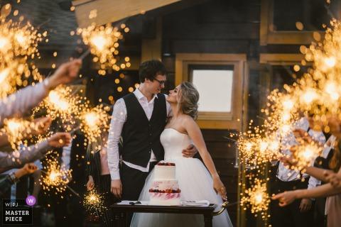 Foto van de bruid en de bruidegom die zich voor hun cake bevinden terwijl omringd door gasten die sterretjes houden door een het huwelijksfotograaf van St. Petersburg, Rusland.