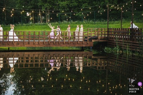 The bride tosses her bouquet on a bridge over water in this photo by a St. Petersburg, Russia wedding photographer.