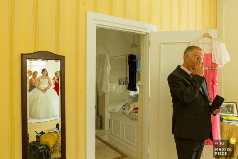 The father of the bride tears up seeing his daughter in her wedding dress in this photo by a Netherlands wedding photographer.