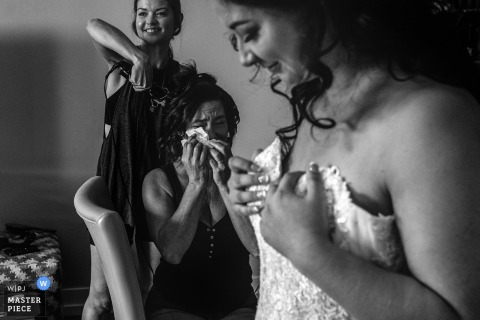 One of the bridesmaids tears up while getting her hair done as the bride puts her dress on in this black and white photo by an Alberta, Canada wedding photographer.
