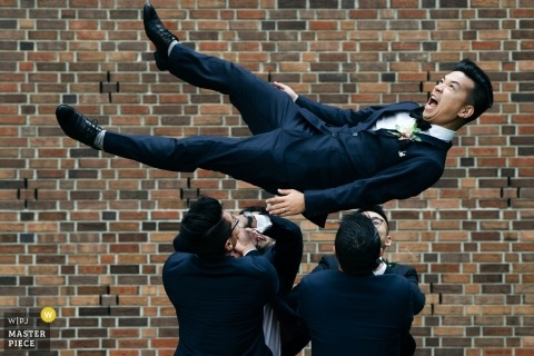 Photo of the groomsmen tossing the groom in the air by an Alberta, Canada wedding photographer.