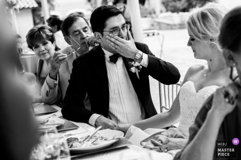 The groom wipes a tear from his eye as he holds his bride's hand in Mexico City, Mexico in this black and white photo by a Rotterdam wedding photographer.