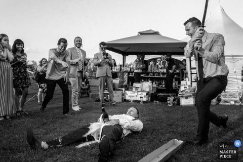 A man lays on the ground holding a bottle of champagne as another takes a swing to open it in this black and white photo by an Alberta, Canada wedding photographer.