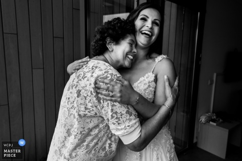 A woman hugs the bride in Ouddorp, The Netherlands in this black and white photo by a Rotterdam wedding photographer.