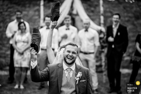 The bride and groom hold a pair of shoes in the air during a game in this black and white photo by a Prague wedding photographer.