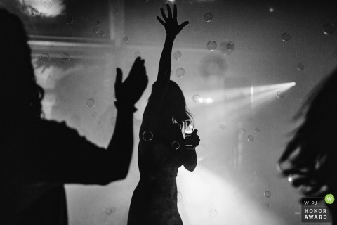 Silhouettierte Braut genießt ein Getränk und die Tanzfläche