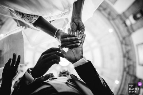 Die Braut setzt den Ring auf ihren Bräutigam im niedrigen Winkel dieses Schwarzweiss-Foto von einem Portugal-Hochzeitsfotografen.