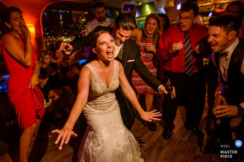 The bride and groom dance on a Lexington yacht in this photo by a New York City wedding photographer.
