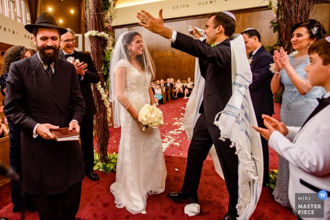 Photo of the groom going to hug his bride in the Sephardic Temple by a New York City wedding photographer.