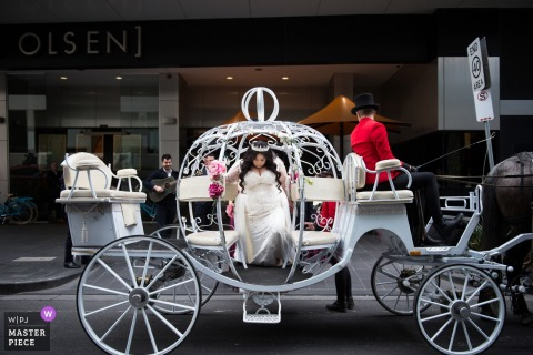 The bride emerges from a pumpkin-shaped horse drawn carriage in this photo by a Victoria, Australia wedding photographer.