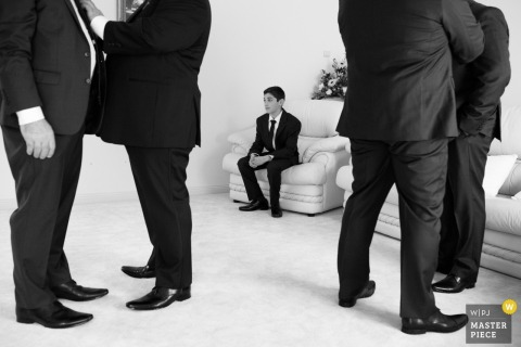 Black and white photo of a young man sitting in a chair as others get ready by a Victoria, Australia wedding photographer.