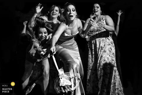 Schwarzweiss-Foto von den Frauen, die nach einem Blumenstrauß von einem Brasilien-Hochzeitsfotografen in Goiânia greifen.