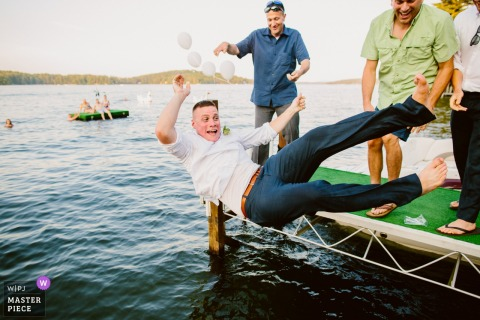 A man falls off a small dock at a private residence in Meredith, NH in this photo by a Boston, MA wedding photographer.