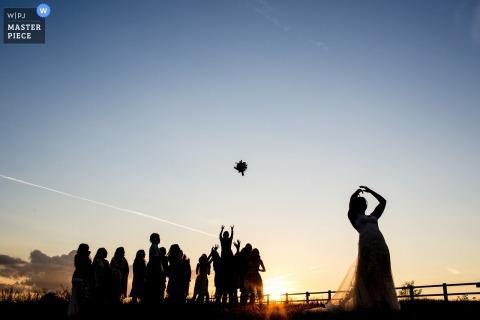 Gaulby, Verenigd Koninkrijk bruiloft fotografie van de bruid toss boeket in de zonsondergang.