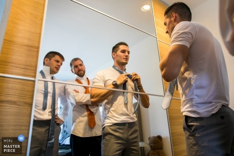 Northamptonshire, United Kingdom groom and two bestmen are working on their ties in the mirror.