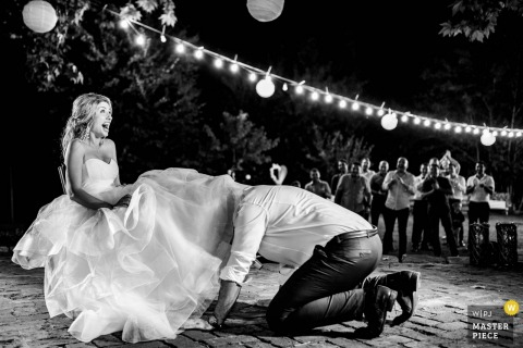 Bulgaria outdoor wedding reception at night - photo of groom getting garter from under the bride's dress.