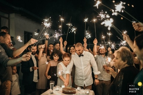 Bulgaria wedding photo of cake cutting under sparklers.