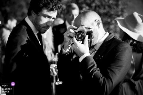 Invité au mariage prenant des photos à l'aide d'un appareil photo avec le capuchon d'objectif toujours activé | Arthingworth, Northants, Royaume-Uni