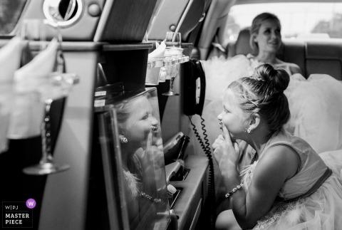 Hochzeitsfoto Kennebunkports, Maine des Blumenmädchens Reflexion auf der Rückseite der Limousine betrachtend.
